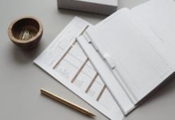 bookwork spread over a desk with a pen